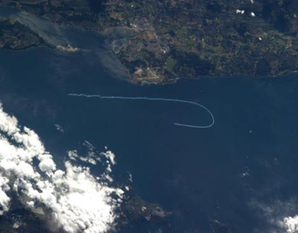 In this photo supplied by NASA, the Snowbirds' smoke trail is seen from space over Georgia Strait.
